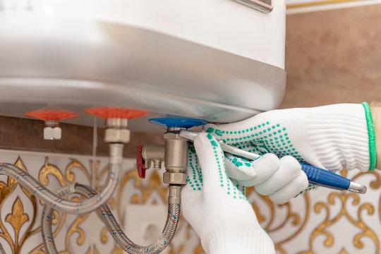 Plumber man installing boiler water heater in bathroom