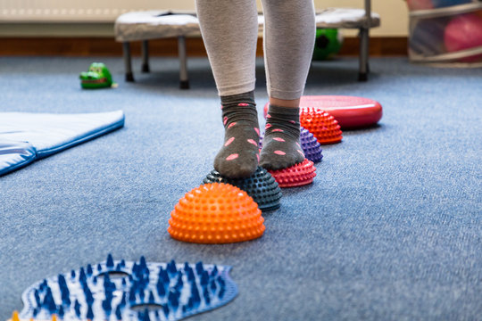 Pediatric Sensory Integration Therapy - a child walking on a sensory mat and pillows (close-up picture)