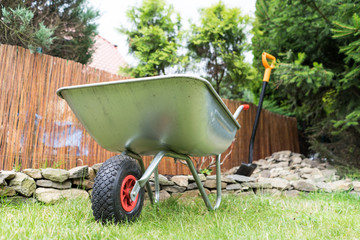 Wheelbarrow On Field In Yard