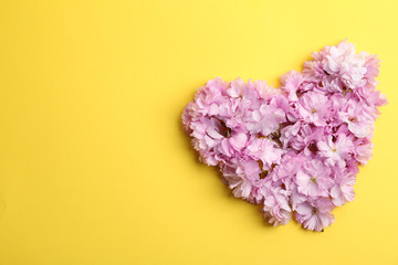 Heart made with sakura blossom on yellow background, space for text. Japanese cherry