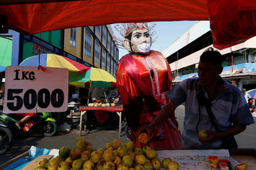 """A large puppet figure called """"Ondel-ondel"""" wears a face mask at traditional market amid the coronavirus disease (COVID-19) outbreak in Jakarta"""
