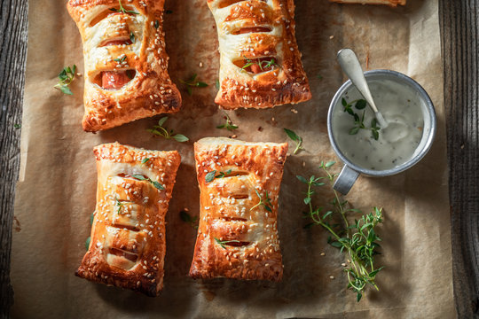 Tasty and fresh sausage roll with herbs and sesame seeds
