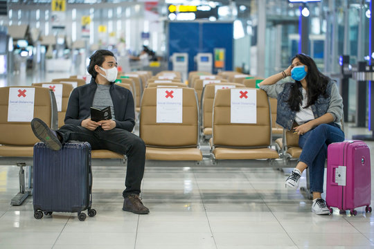 Backpacker travelers Asian women wearing masks covid 19 disease Prevention An sitting, creating a social distancing while waiting check in with smartphone in the airport terminal.
