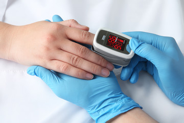 Doctor examining patient with modern fingertip pulse oximeter in bed, closeup