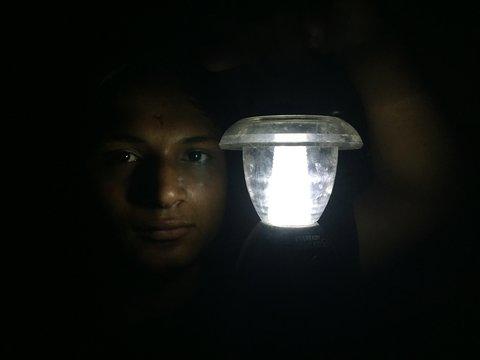 Portrait Of Man Holding Illuminated Lighting Equipment In Darkroom