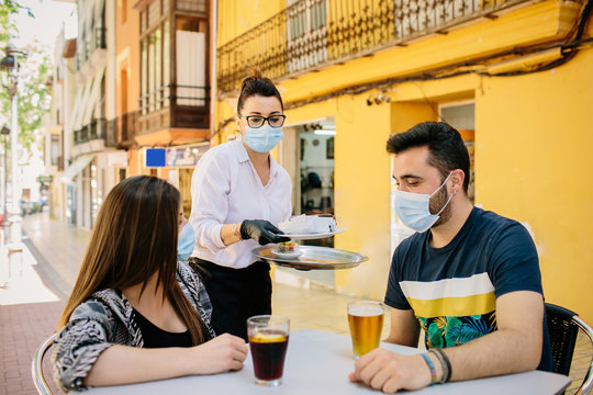 Waitress from a bar in Spain serves food and drinks to customers on her terrace. Everyone wears a mask to protect themselves from contagion. Phase one of the de-escalation. Social distance
