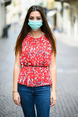 Beautiful girl alone young woman looking at camera and wearing a mask, coronavirus concept