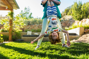 teenager sister holding her younger brother upside down on green lawn at sunset