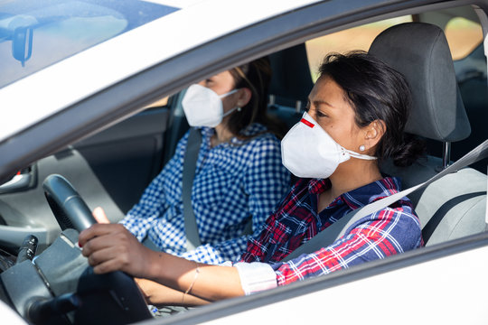 Women wearing personal protective equipment while driving a car