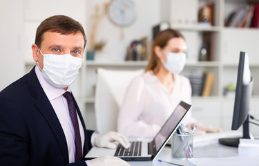 Portrait of businessman in protective medical mask at office