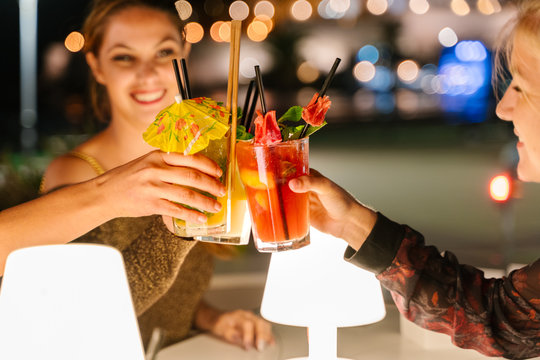 Selective focus on the glasses of three young women making a toast with cocktails on a terrace at night