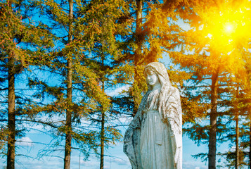 Fotomurales - Very old and ancient stone statue of Virgin Mary in sunshine against blue sky and trees.