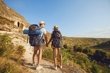 Hiking couple with backpack walking on hike in nature