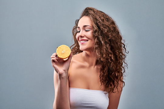 Young happy woman showing a fresh lemon on grey background