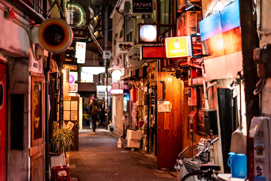 Tokyo, Japan - April 3, 2019: Shinjuku ward downtown with Golden Gai narrow alley lane street with izakaya restaurants at night and signs