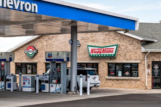 Spanish Fork, USA - July 29, 2019: Krispy Kreme doughnuts donut chain business facade exterior entrance sign in Utah by Chevron gas station pump
