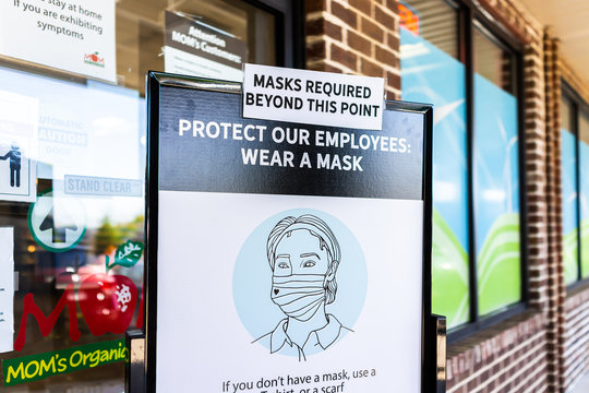 Herndon, USA - May 7, 2020: Mom's Organic Market store in Virginia with customer sign to wear face mask covering beyond this point to protect employees during Covid-19 coronavirus outbreak