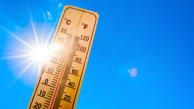 Summer background - blue sky with bright sun and thermometer