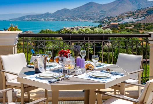 Table with fruits and wine on a summer terrace with sea and mountain views in Crete in Greece.