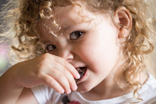 Cute little toddler eating a brownie