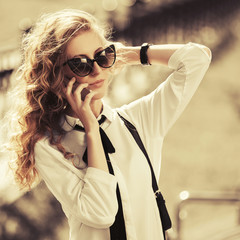 Blonde fashion business woman in sunglasses calling on cell phone