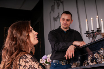 Woman playing on a piano while man standing near