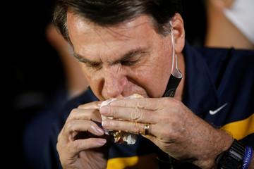 Brazil's President Jair Bolsonaro eats a hotdog in a street cafeteria, amid the coronavirus disease (COVID-19) outbreak, in Brasilia