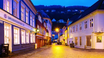 Wall Mural - Bergen, Norway. View of old historical fishermen houses in Bergen, Norway during the sunrise. Time-lapse of empty streets in the morning after the rain, zoom in