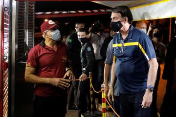 Brazil's President Jair Bolsonaro buys a hotdog in a street cafeteria, amid the coronavirus disease (COVID-19) outbreak, in Brasilia