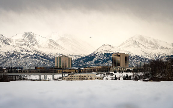 Beautiful mountains of Chugach Park behind the streets, houses & buildings of Anchorage, Alaska. Taken from Port Ship Creek Small Boat Launch during the winter when covered with snow and cloudy.