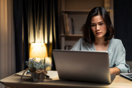 Asian business woman does overtime working from home in living room at late night due to covid19 pandemic. Girl feeling tired and serious face to complete jobs, looking and typing on computer laptop.