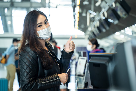 Asian female traveler holding passport at customer check in of airline service counter. New normal, woman wearing face mask when traveling by airplane transportation to prevent covid19 virus infection