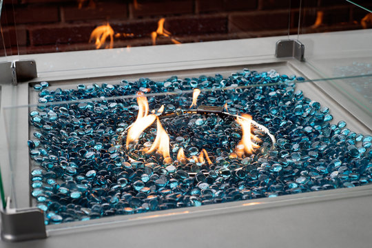 Modern lit gas fire pit with blue glass marbles in an outdoor setting