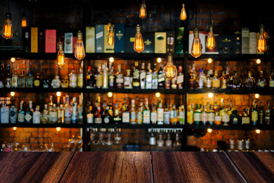Wooden table with soft liquor bar background