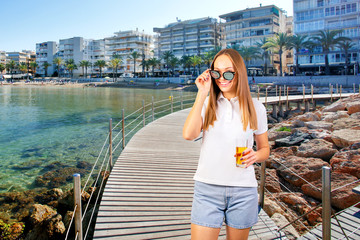 Smiling woman enjoying sunny day at seaside promenade of Salou, Spain. Young woman drinking cocktail on the beach.