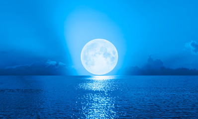Wall Mural - Full moon rising over empty ocean at night with power wave