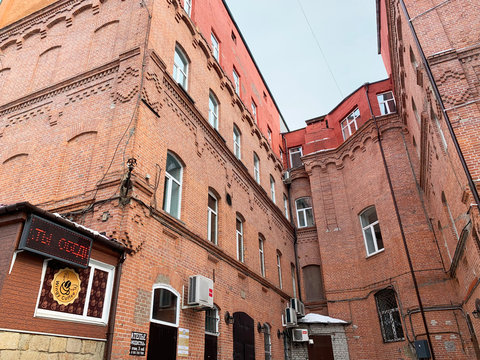Vladivostok, Russia, March, 01,2020. Red-brick houses that form the  courtyard of Old Gum, Vladivostok, Russia. Wingy coffee cafe
