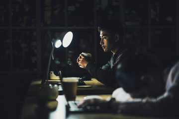 Asian businessman working hard late with his technology laptop in office, customer service and call center department, hard worker and overtime, her colleagues sleepy, low light environment, Fotobehang