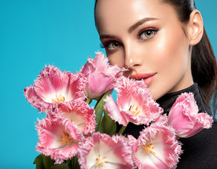 Beautiful white girl with flowers. Stunning brunette girl with big bouquet flowers of pink tulips....