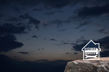 Hammer and wrench with house flat icon on rock mountain over sunset sky, Business home service concept