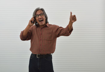 Happy asian senior businessman in red casual shirt and blue jeans using smart mobile phone and making thumbs up standing over white wall, Business confident and success concept