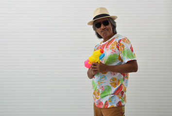 Happy elderly traveler asian man wearing summer shirt, straw hat and sunglasses holding colorful squirt water gun standing over white wall, Funny face expression pose, Water festival concept