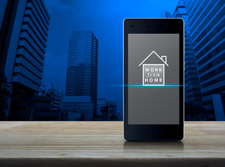 Work from home flat icon on modern smart mobile phone screen on wooden table over office city tower and skyscraper, Business social distancing online concept