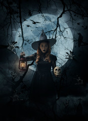 Halloween witch holding ancient lamp and skull standing over zombie hand, cross, church, crow, birds, dead tree, full moon and cloudy spooky sky, Halloween mystery concept