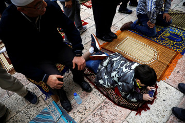 A boy plays with a mobile phone as Palestinian men stand next to their prayer mats while performing Eid al-Fitr prayers amid the coronavirus disease restrictions in Jerusalem's Old City