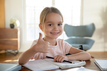 Headshot portrait of happy little girl sit at desk studying show thumbs recommending good course, smiling small schoolgirl give recommendation to school program or training, education concept