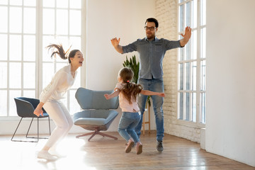 Happy young family with little daughter have fun jumping in living room entertain on weekend at...