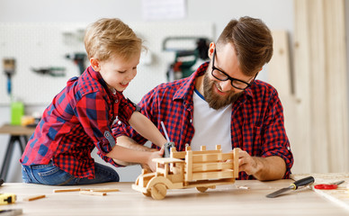 Cheerful man with kid making wooden toys in workshop.