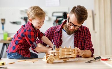 Keuken foto achterwand Wanddecoratie met eigen foto Cheerful man with kid making wooden toys in workshop.