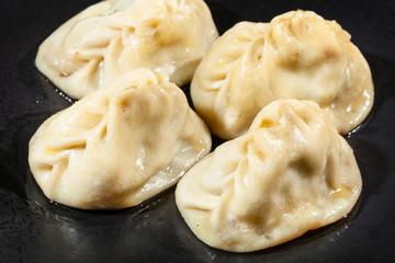 portion of Manti (type of dumpling in turkic cuisine) on black plate